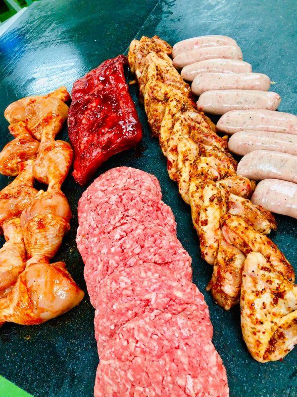 Display of seasoned steak burgesr, chicken drumsticks, Cumberland sausages, pork ribs, and chicken wings