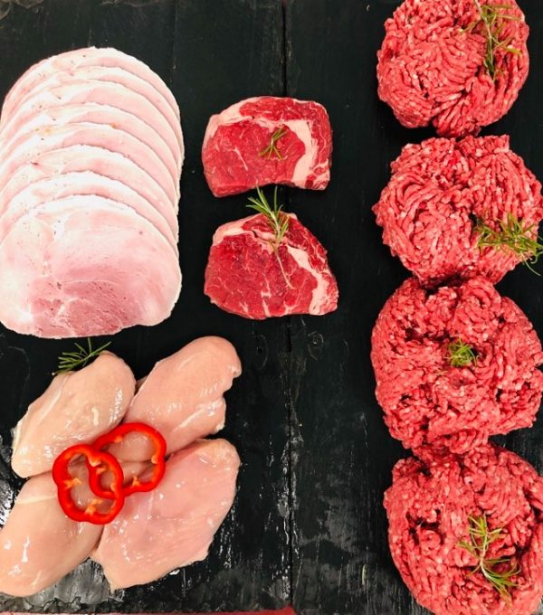 Display of fresh ribeye steaks, chicken breast fillets, beef mince and gammon ham slices, garnished with sliced red peppers and sprigs of fresh rosemary