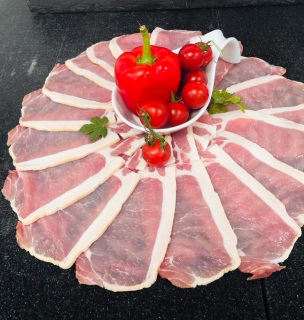 Circular arrangement of fresh unsmoked back bacon rashers with bowl at centre containing whole red pepper and cherry tomatoes