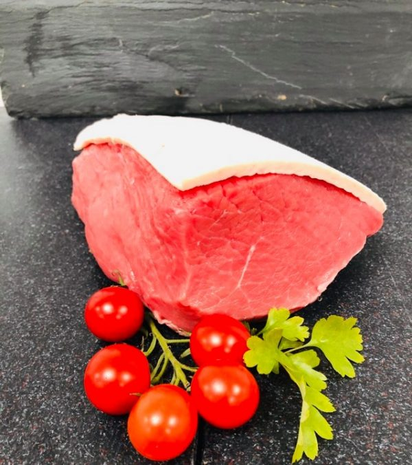Fresh beef topside joint garnished with vine of cherry tomatoes and flat-leaf parsley