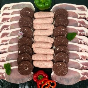 Display of fresh bacon, Cumberland sausages, and sliced black pudding garnished with fresh red and green peppers