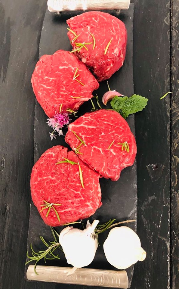 Display of four fresh fillet steaks garnished with whole garlic bulbs, mint, and sprigs of rosemary