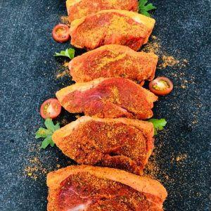 Six fresh lamb steaks dusted with seasoning and garnished with cherry tomatoes and flat-leaf parsley