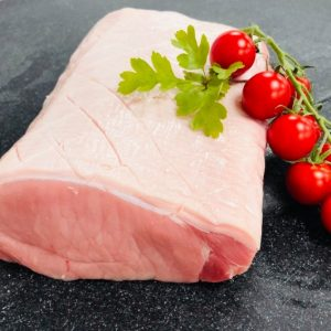 Fresh pork loin joint with scored rind. Garnished with vine of cherry tomatoes and flat-leaf parsley