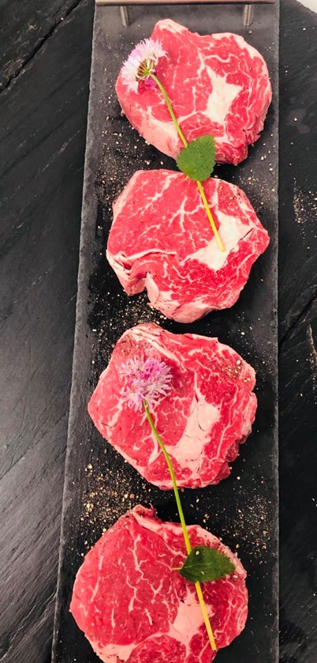 Display of four fresh ribeye steaks garnished with herbs and disted with ground salt and pepper