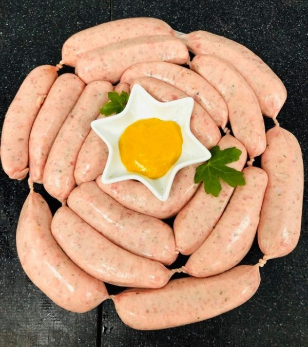 String of Cumberland sausages arranged in a ring with bowl of mustard at the centre