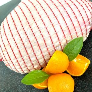 Trussed turkey breast joint garnished with orange quarters