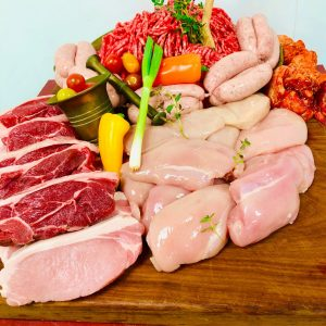 Assortment of fresh meats garnished with fresh herbs, spring onion and whole yellow pepper