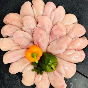 Circular display of fresh chicken breast fillets garnished with two whole peppers