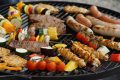 Selection of meats and vegetables cooking on barbecue grill