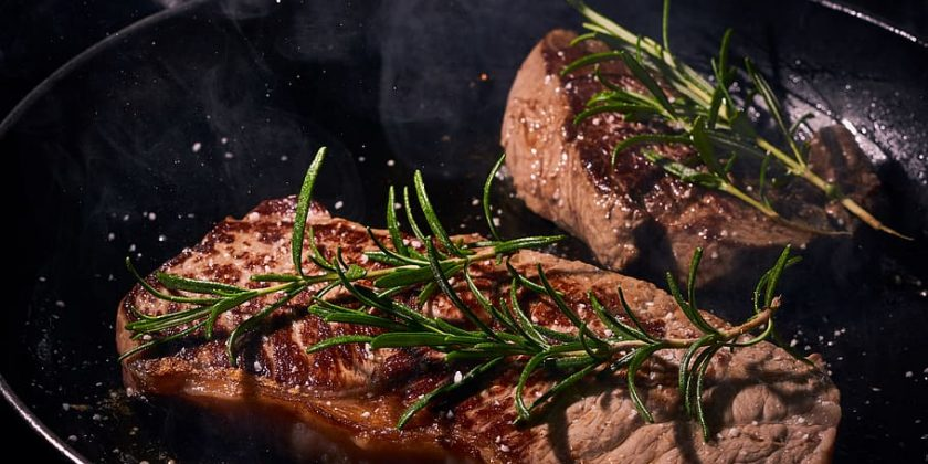 Two sirloin steaks in frying pan with rosemary sprigs